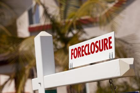 Close-up Foreclosure Real Estate Sign in Front of House.